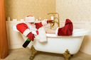 Funny drunk Santa Claus with alcohol bottle in hand sleeping in a bath. Christmas humor