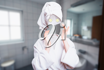 Girl in white bathrobe with towel on head with cucumbers on eyes touch her invisible face. Invisibility fantasy concept, transparent female person. Personal hygiene advertising or marketing