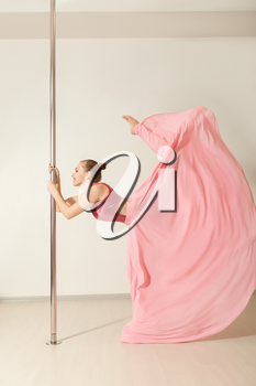 Slim professional poledance girl posing in beautiful pink dress. Sexy strip dancer exercising with pole in dance studio