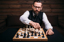 Serious male chess player in glasses makes victory move. Win strategy concept