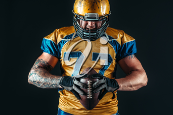 Muscular american football player in uniform and helmet holds ball in hands, black background. Contact sport
