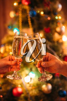 Two hands clink glasses with champagne, christmas tradition, romantic celebration. Xmas symbol to drink sparkling wine