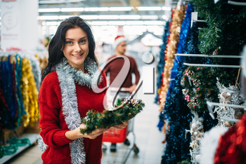 Young couple purchasing christmas holiday decorations in supermarket, family tradition. December shopping