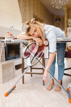 Young tired housewife slepping on the ironing board. Woman doing housework at home. Female person irons the clothes in the house