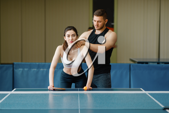 Man doing massage to woman, ping pong training indoors. Couple in sportswear holds rackets and plays table tennis in gym