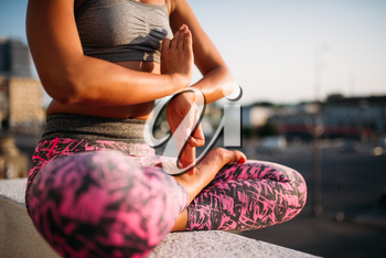 Female person body in yoga pose, cityscape on background. Yogi training outdoors, concentration workout