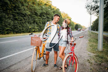 Young man and woman kissing on romantic date. Happy love couple with vintage bike. Boyfriend and girlfriend together outdoor, retro bicycle