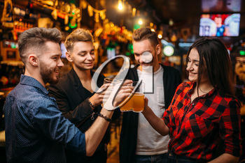 Happy football fans raised their glasses with beer at the bar counter in a sport pub, victory celebration