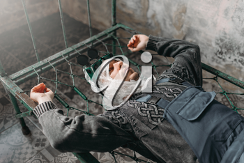 Freak man wraps his head in packaging film and lies in bed, grunge room interior. Mad male person in abandoned house, crazy guy