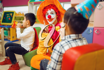 Funny clown play with cheerful children together. Birthday party celebrating in playroom, baby holiday in playground. Childhood happiness, childish leisure