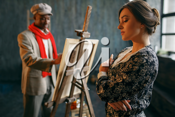 Portrait painter at the easel draws female model. Male artist standing at his workplace, creative master works in workshop