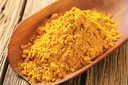 Heap of curry powder on a wooden scoop