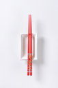 A pair of red chopsticks on empty soy sauce dish