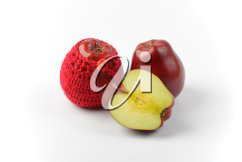 two and a half red apples, one in crochet apple cozy