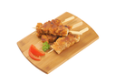 four spicy chicken skewers on wooden cutting board