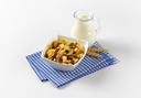 bowl of mixed breakfast cereals and jug of milk on blue checkered dishtowel