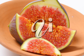 close up of fresh sliced fig on terracotta bowl