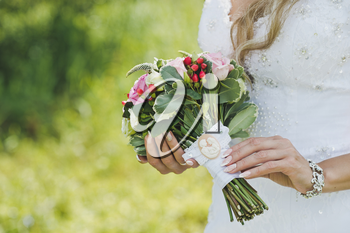 Bouquet of white and pink roses in hands of bride.