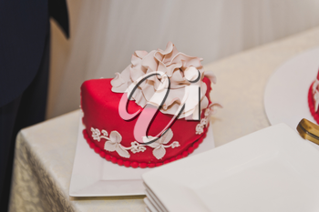 Red cake with beige flowers.