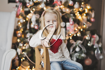 Portrait of a child on a background of Christmas tree decorated with balls.