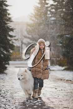 Portrait of a girl with a dog walking along the autumn alley.