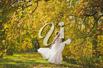 The bride happily spinning in the developing dress on the edge of the bright autumn forest.