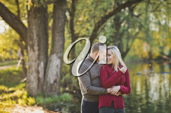 Guy and girl hugging standing on the shore of the pond.