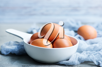 raw eggs in white bowl and on a table