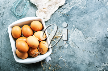 raw eggs in bowl and on a table