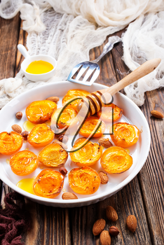 baked apricots with honey and nuts on a table