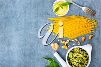 raw pasta cheese and pesto sauce in bowl