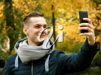 Cute young man with smartphone in autumn park
