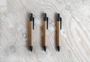 Three pens on a light wooden background. Template for design presentations and portfolios. Top view.