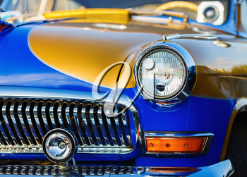 Close-up of vintage classic car. Bright colored retro car. headlight of a vintage car. Selective focus on the car's headlight.