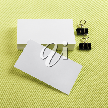 Stack of blank business cards on a green background. Template for branding identity. Top view.