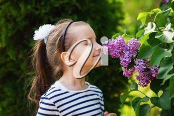 Little girl child smelling lilac flowers in the garden. Selective focus.