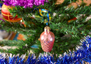 Christmas toys and ornaments on the Christmas tree. Tinsel, balls and toys decorated fir.