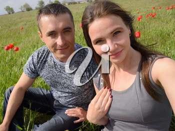 A girl and a guy are sitting together outdoors. Young couple in a field of tulips. Relationships of young people.