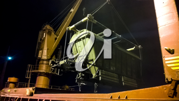 Industrial seaport at night. The rotation of the car with grain using a tower crane.