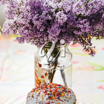 Bouquet of lilacs near Easter cakes and colored eggs