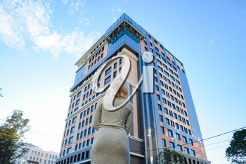 A girl with a beautiful figure in a gray dress near a tall building