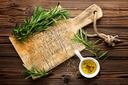Culinary background with wooden board and cooking ingredients, olive oil and rosemary, above view, space for a text
