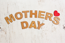 Mothers Day with wooden letters on an old white wooden background