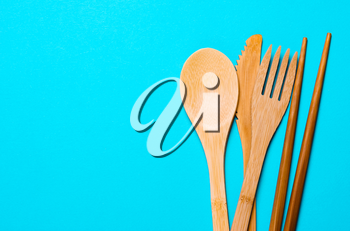 Natural, ecological, Organic wooden fork, spoon, cutlery on a blue background. Concept zero waste, environmental pollution.