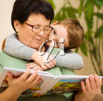Grandmother is reading book with her grandson, indoors
