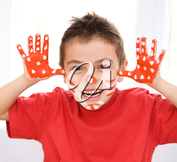Portrait of a cute boy showing her hands painted in bright colors