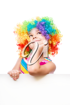 Cute girl in clown wig is holding blank banner, isolated over white