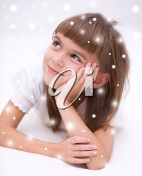 Cute girl is daydreaming lying on the floor, over snowy background