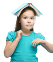 Cute girl is reading book - school, education concept, isolated over white