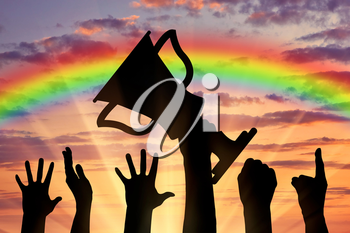 Winning the cup sport. Human hands holding the cup on the background of rainbow sunset